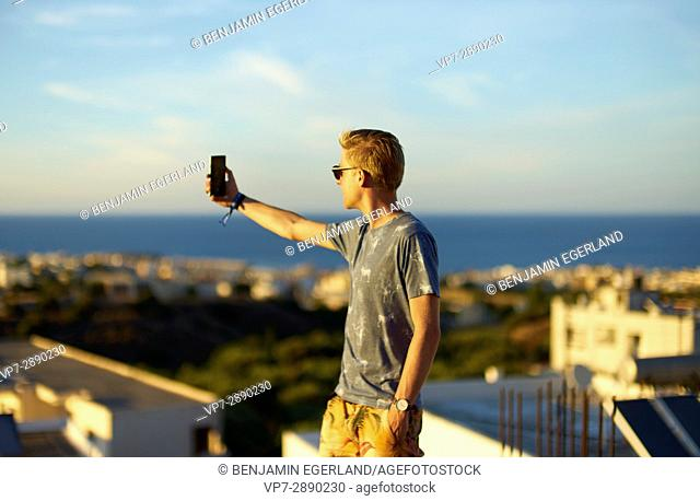young man taking selfie during sunset in holiday destination Hersonissos, Crete, Greece