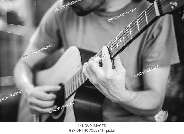 Young Man Looking Down Playing Acoustic Guitar