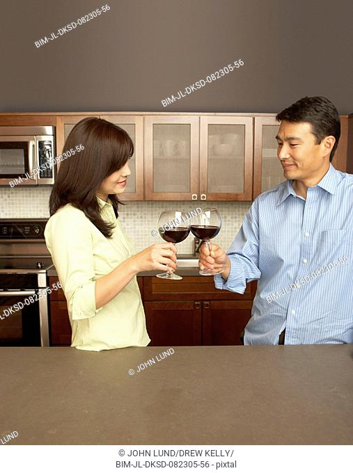 Young couple toasting each other with wine