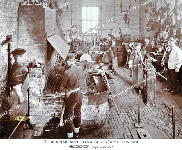 Boys at work in the smith's shop, Feltham Industrial School, Feltham, London, 1908. Boys in aprons learning metalwork in the smithy