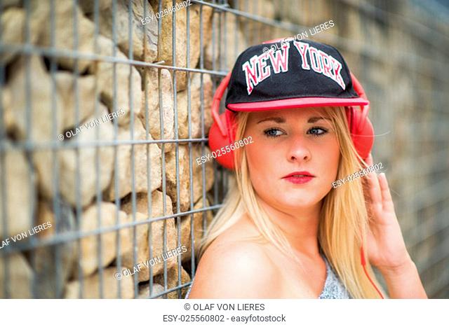 girl with baseball cap standing at stone wall