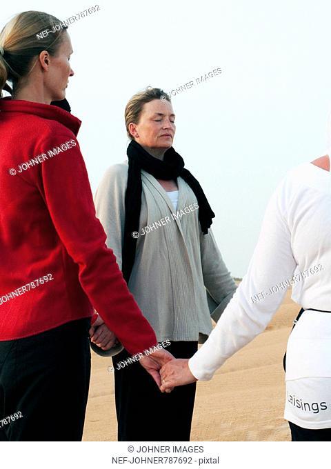 Women standing together meditating, Tunisia