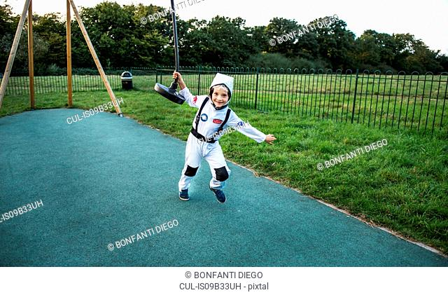Portrait of boy in astronaut costume pulling playground zip wire
