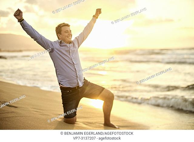 Young man kneeling on Potamos beach, wearing business shirt, in holiday destination Malia, Crete, Greece