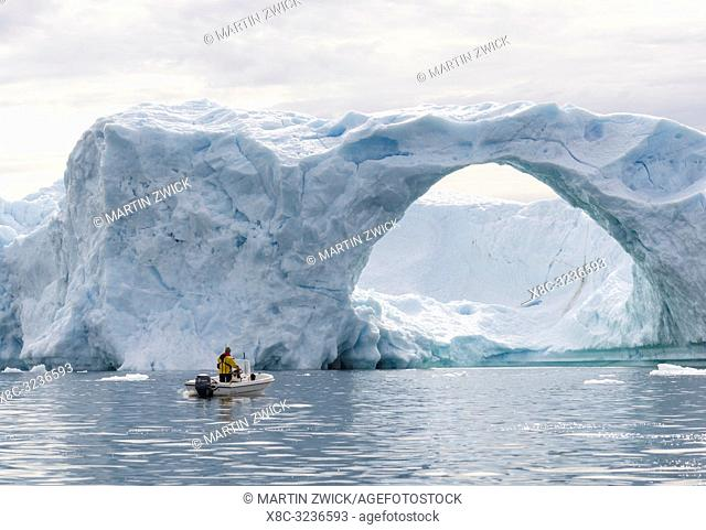 Icebergs in the Disko Bay, local hunter hunting for seal in small boat. Greenland, Denmark, August