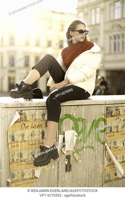 young cool woman sitting on distribution board, wearing sunglasses, in city Cottbus, Brandenburg, Germany