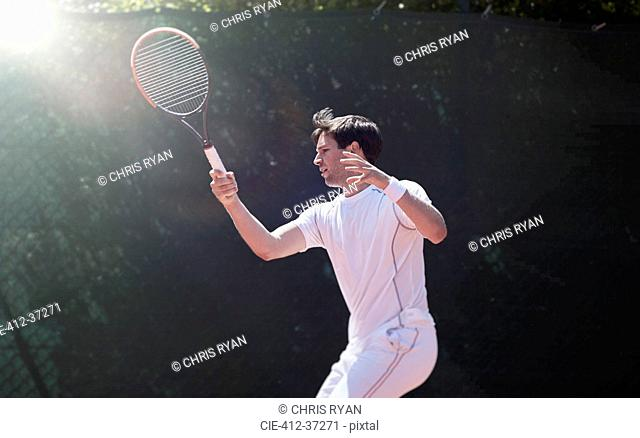Young male tennis player playing tennis, swinging tennis racket
