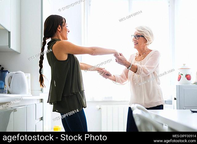 Grandmother and granddaughter holding hands while dancing together in kitchen at home