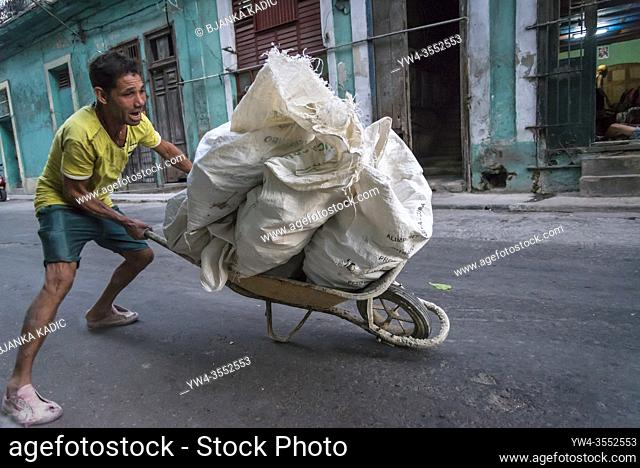 Man transporting stones for building material in a wheelbarrow, the wheelbarrow at the point of tipping over, Havana Centro district, Havana, Cuba