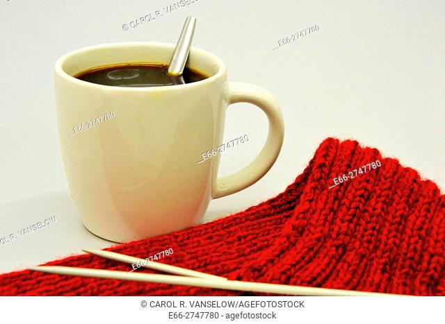 Cup of coffee next to knitting