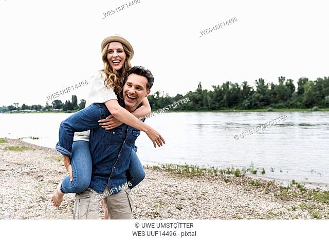 Happy man carrying girlfriend piggyback at the riverside