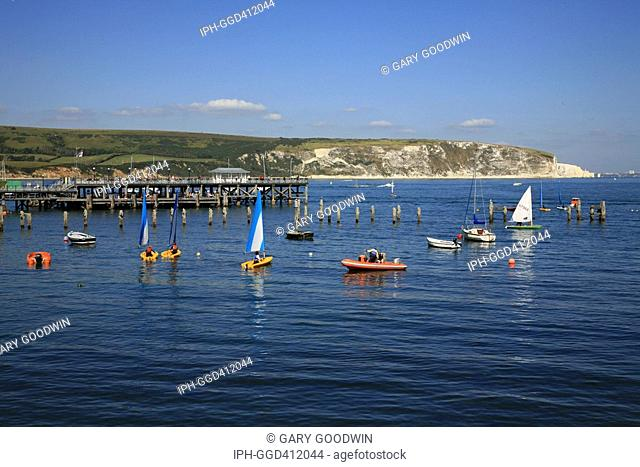 Swanage - Sailing near the pier in the popular seaside resort with the chalk cliffs of Ballard Point in the distance