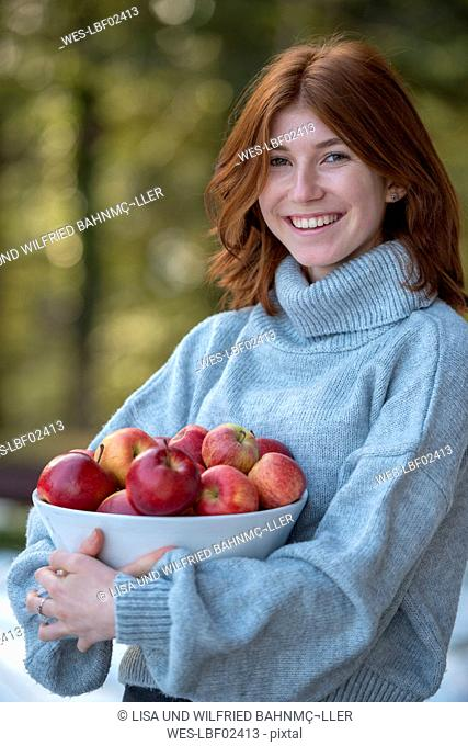 Portrait of redheaded teenage girl holding bowl of apples