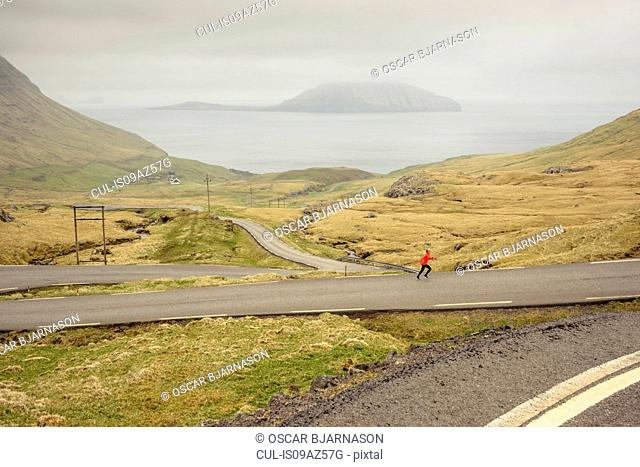 Runner jogging on country road, Nororadalur, Faroe Islands