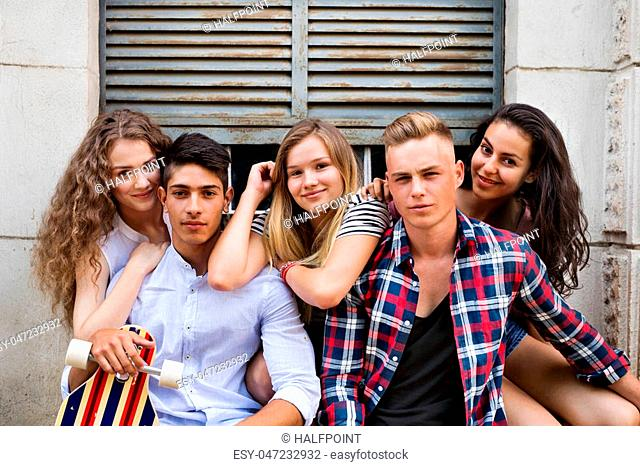 Group of attractive teenage students posing in front of old university