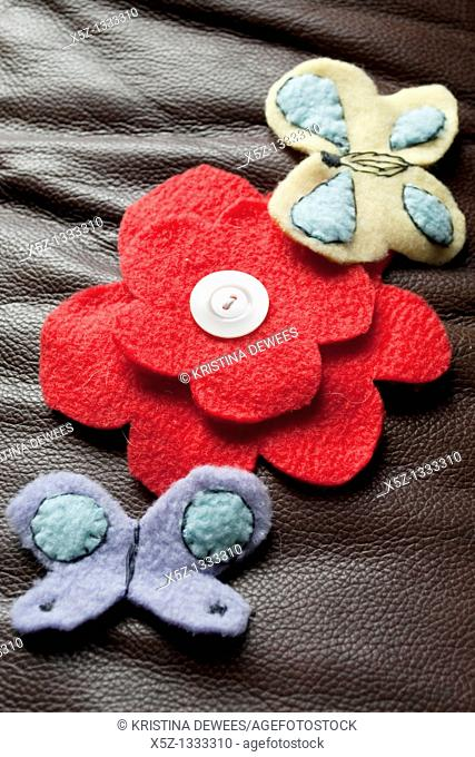 A red fleece flower with a button center surrounded by fleece butterflies