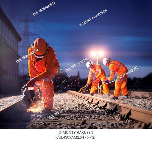 Railway maintenance workers using grinder on track at night