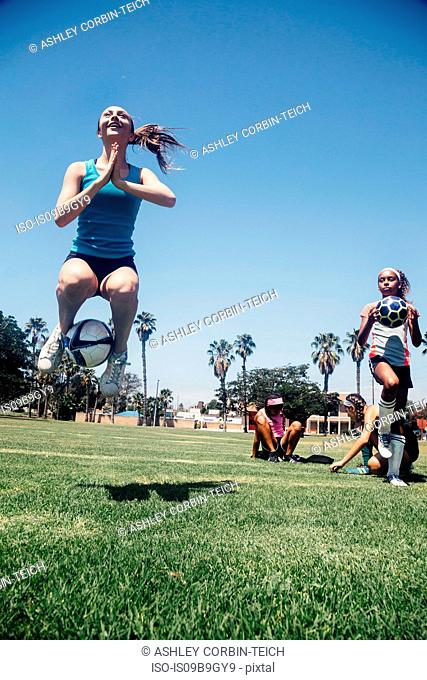 Schoolgirl jumping with soccer ball on school sports field