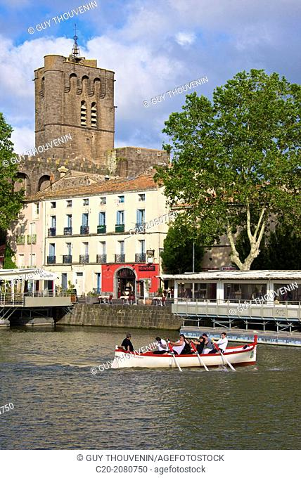 Fortified Ancienne cathédrale St Etienne, 12thc., built in black lava,and river banks with restaurants along Herault river, and jousters training, AGDE town