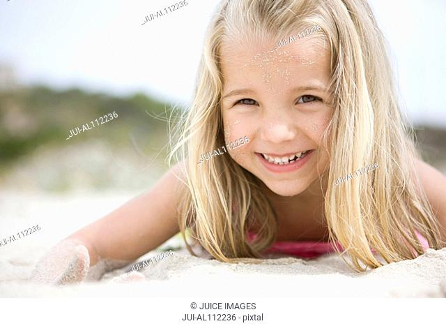 Portrait of young girl smiling in sand