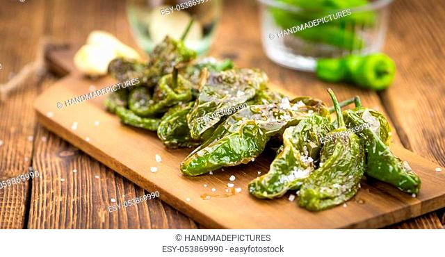 Pimientos de Padron on an old wooden table as detailed close-up shot; selective focus