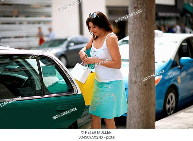 Woman sitting with shopping bags struggling to get into taxi, Los Angeles, California, USA