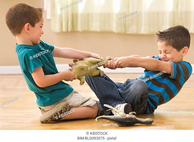 Caucasian boys fighting over dinosaurs