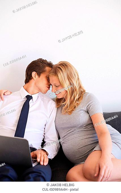 Romantic man whispering to pregnant girlfriend on sofa