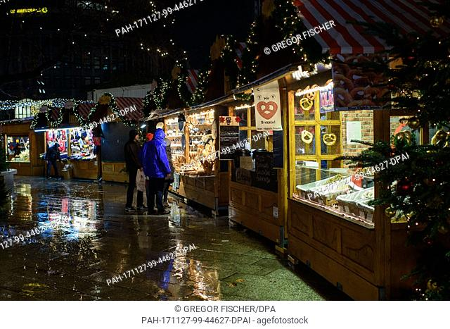 Visitors looking at the goods on sale at the Christmas market at Breitscheidplatz in Berlin, Germany, 27 November 2017. Photo: Gregor Fischer/dpa