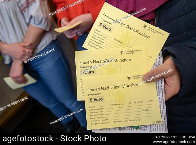 27 February 2020, Bavaria, Munich: Three women hold the first night taxi vouchers for women in the state capital in their hands
