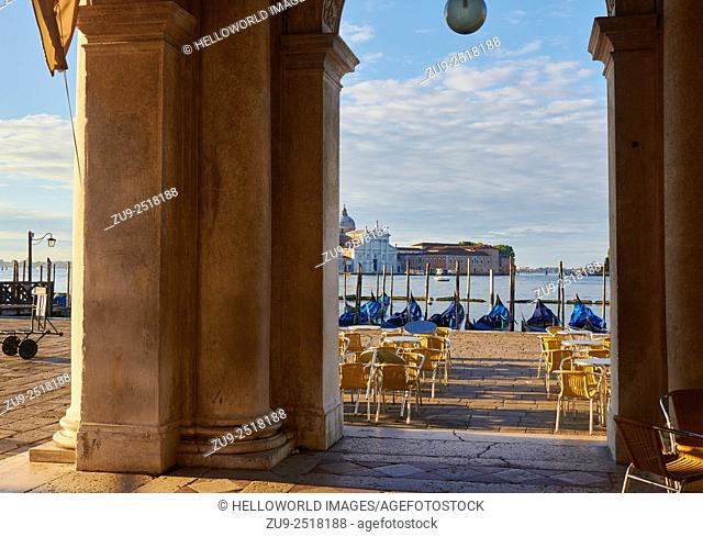 Dawn view of Basilica di San Giorgio Maggiore, gondolas and tables and chairs from colonnaded passageway, St Mark's Square, Venice, Veneto, Italy, Europe