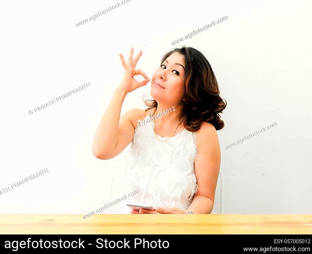 Beautiful woman showing OK hand sign smiling happy against white background.