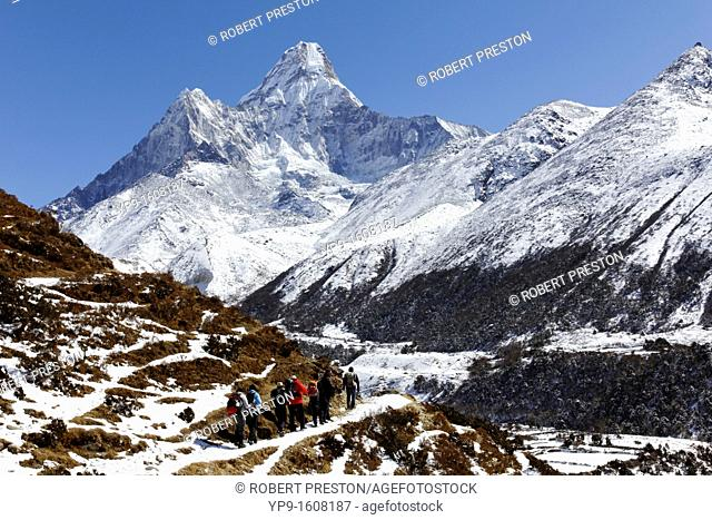 Trekkers walking below Ama Dablam mountain, Everest Region, Nepal