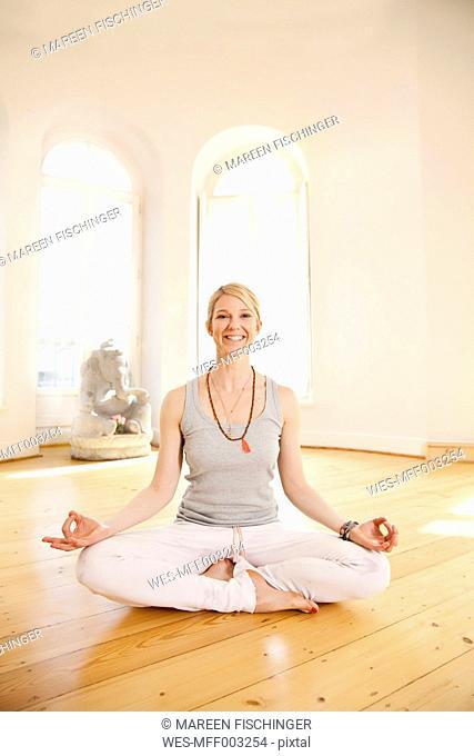 Smiling woman in sunny yoga studio holding Lotus pose