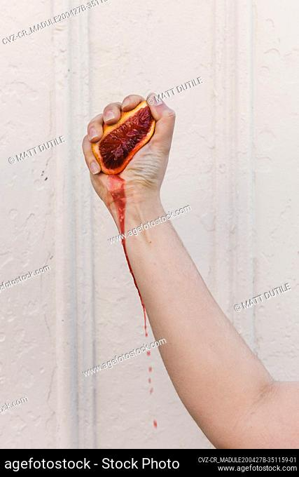 Woman's hand squeezing the juice out of a blood orange and dripping