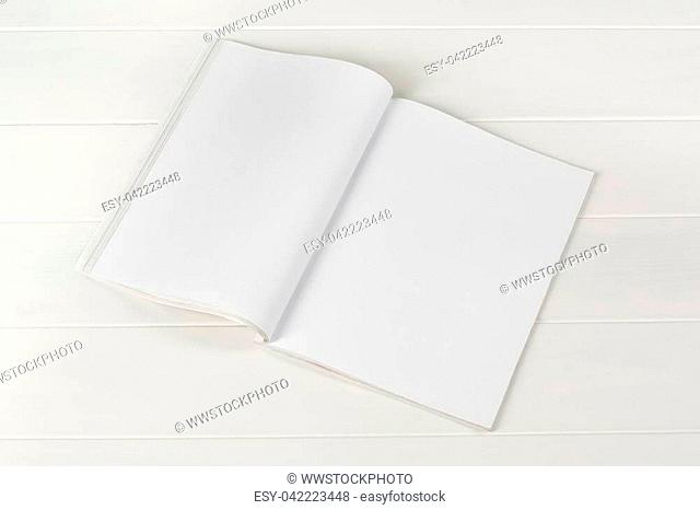 Mock-up magazine or catalog on white wooden table. Blank page or notepad on wood background. Blank page or notepad for mockups or simulations