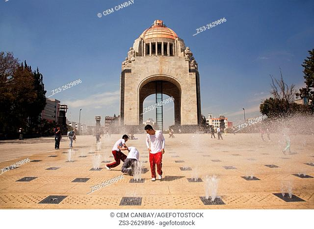 Student playing with the water near the Monument dedicated to the Mexican Revolution (Monumento dedicado a la Revolucion Mexicana), Mexico City, Mexico
