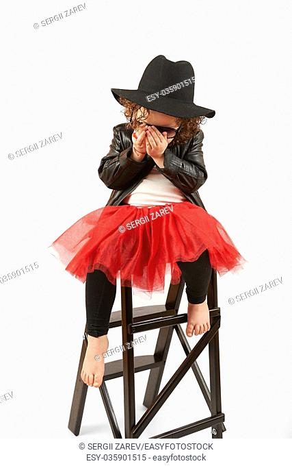 Little girl with black hat sitting on a high stool and shy