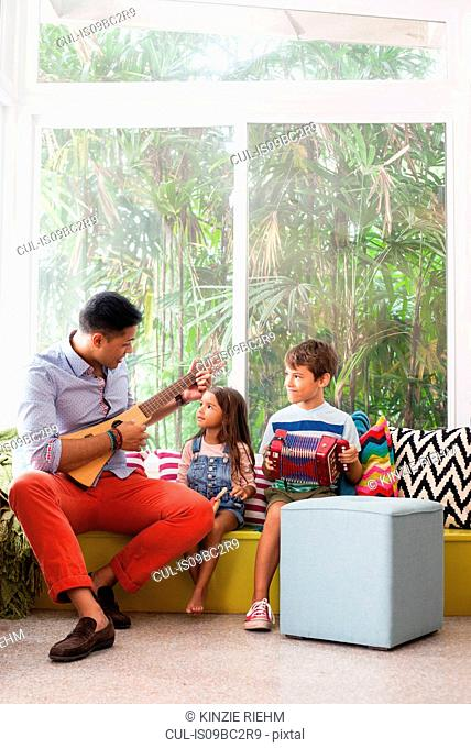 Girl and boy practicing music with teacher on window seat