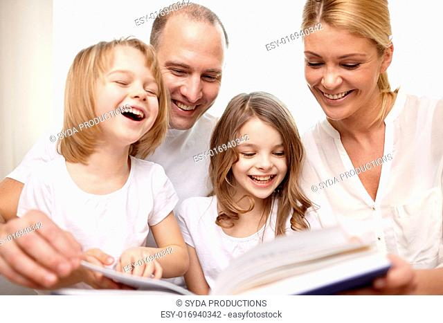 family, childhood, literature and people - happy mother, father and little girls reading book and laughing at home