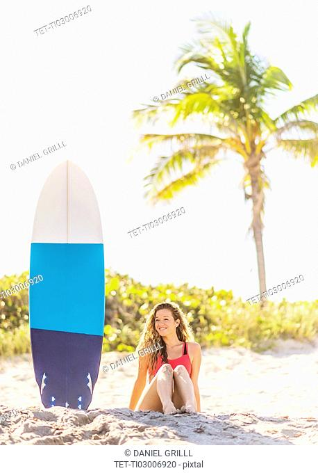 Portrait of young woman sitting near surfboard on beach
