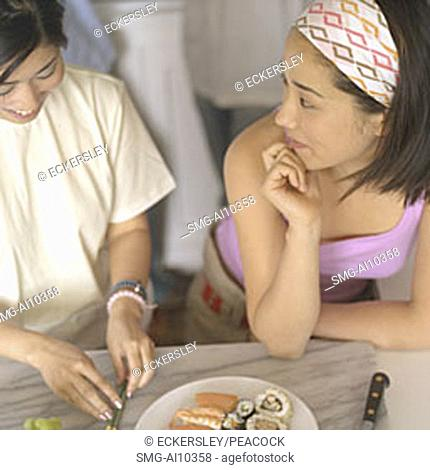 Two young women talking, one slicing fruit