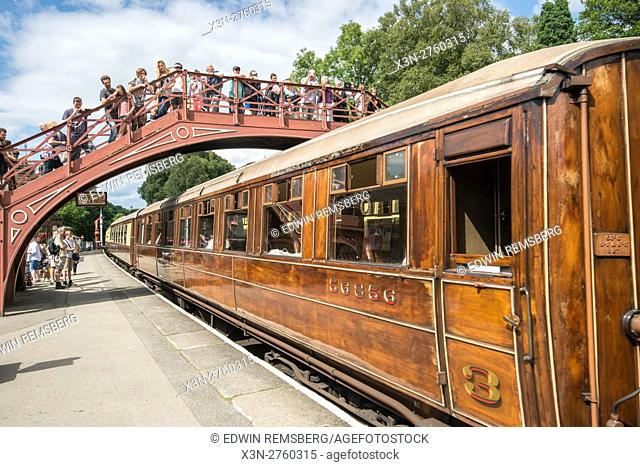 UK, England, Yorkshire - a train arrives at the Goathland railway station while passengers wait along the platform and above on a bridge