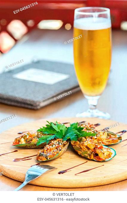Vegetable caviar sprinkled with sesame seeds on thin cucumber slices with fresh parsley and sweet and sour sauce on a background of a blurry glass with beer
