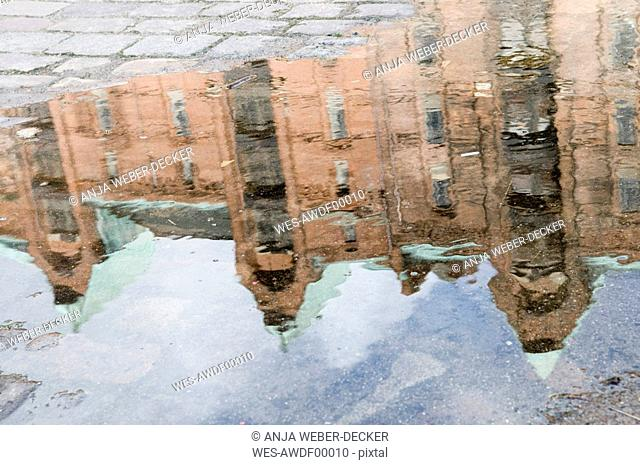 Germany, Hamburg, Old warehouse district, buildings reflected in puddle on road