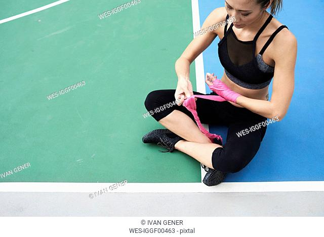 Fit woman wrapping hands for boxing