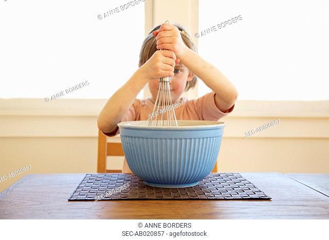 Girl (4-5) hitting pan with whisk