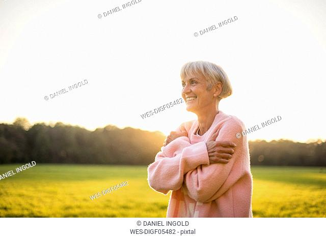 Smiling senior woman standing on rural meadow at sunset