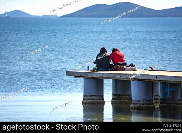 Couple sitting on the end of the jetty at Los Alcazares in Murcia Spain