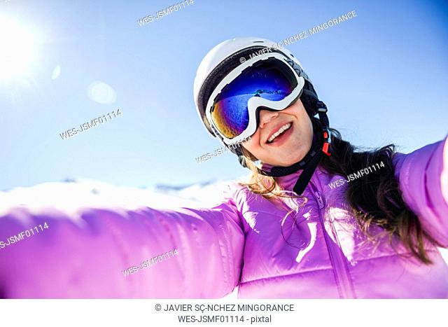 Selfie of happy young woman in ski clothes